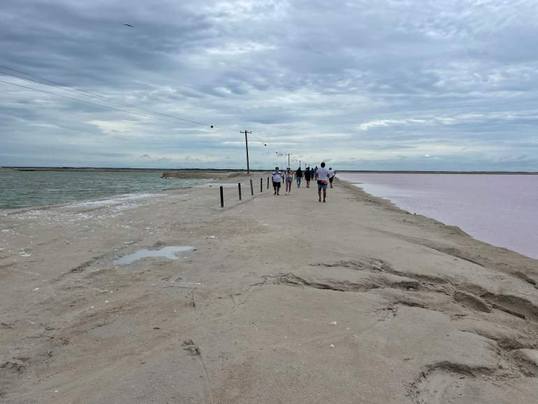 An accessible dirt path with the ocean on the left side and a pink lake on the right side.