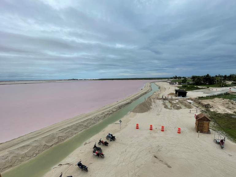 A green channel running beside the pink Las Coloradas lake.