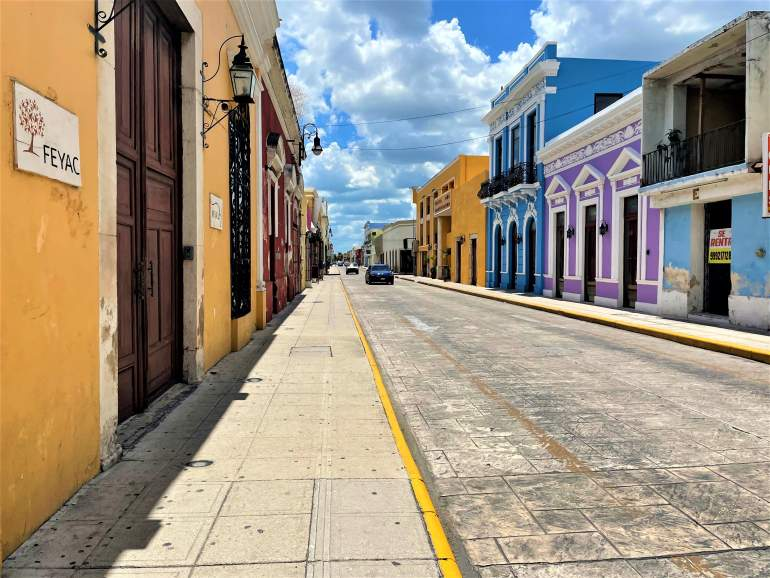 A wheelchair accessible sidewalk by colorful buildings on Calle 59 in Merida.