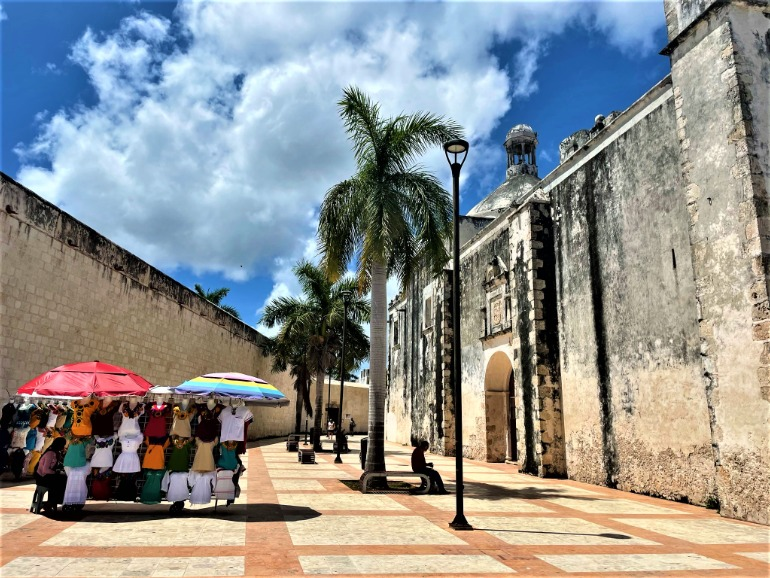 Vendors selling shirts beside Campeche's old wall.