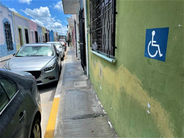 A narrow sidewalk in Campeche beside a supposedly wheelchair accessible parking spot.