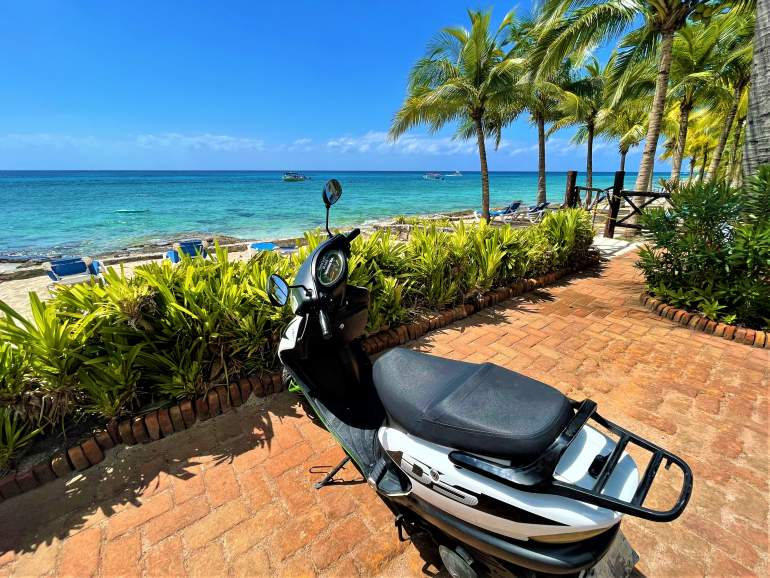 A scooter parked in front of Cozumel's coastline.