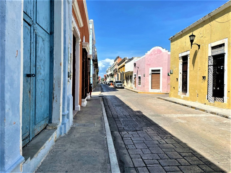 A fairly narrow sidewalk in Campeche with colorful buildings.