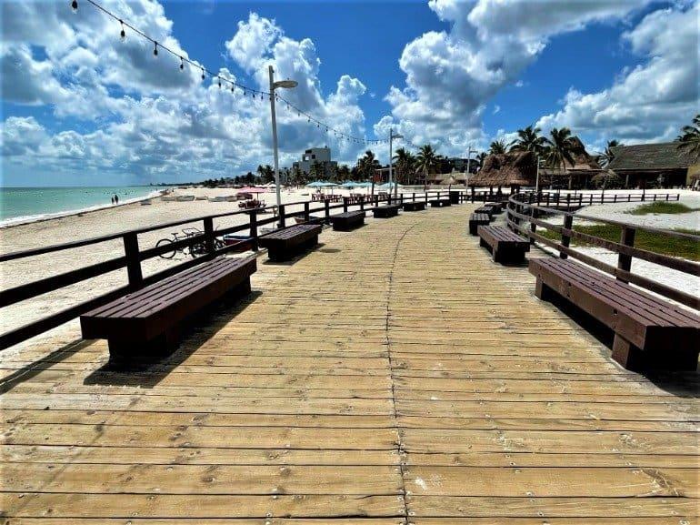 A wooden boardwalk raised above Progreso beach.