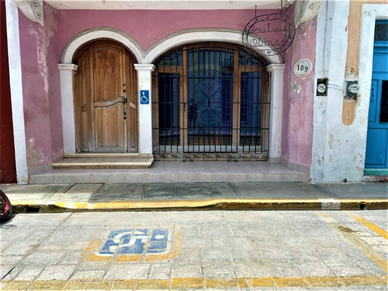 An accessible parking space in front of a pink house.
